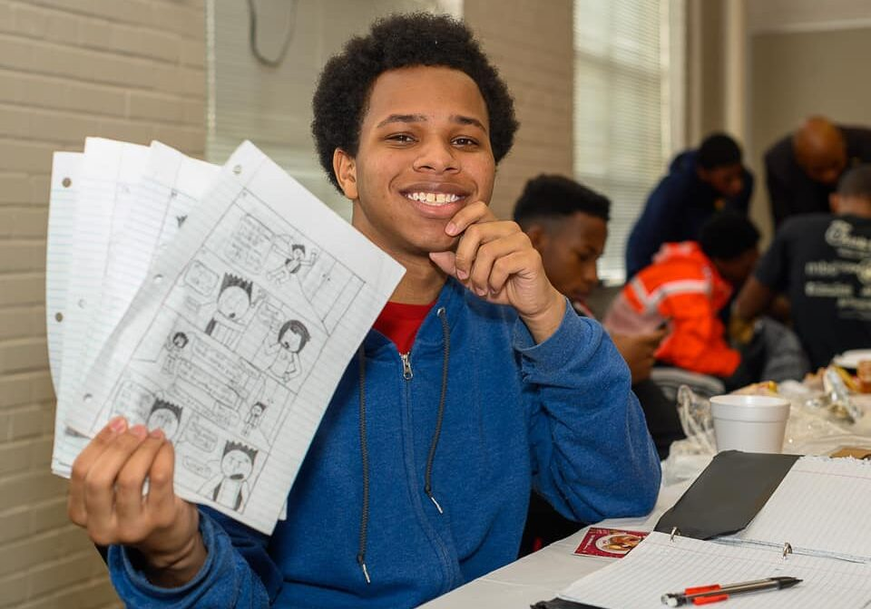 Boy holding up paper with drawings on it.