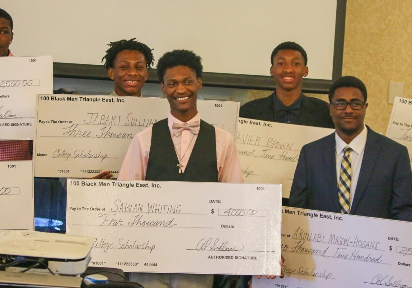 A group of young men holding oversized checks